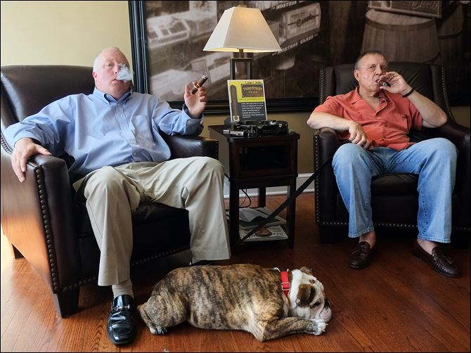 n4cigardog-1 John Henry, left, and Dave Webb, two of the co-owners of  Third Street Cigar, sit back and enjoy a quiet moment at their Waterville store in their dogged pursuit of a place for fellow aficionados.