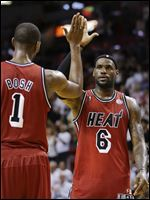 Miami Heat's Chris Bosh (1) and LeBron James (6) celebrate an overtime win against the Sacramento Kings, in Miami. during last NBA season.