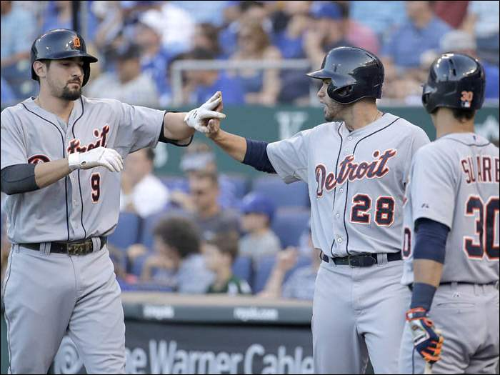 Detroit Tigers' Nick Castellanos (9) and J.D. Martinez (28) celebrate after Martinez scored on a sacrifice fly hit by Castellanos.