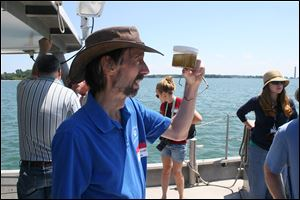 Rick Stumpf, NOAA oceanographer and lead researcher of its algae forecast, looks at a Lake Erie water sample near Put-in-Bay.