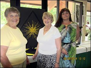 JoAnne Searle, left, was chairman of the Garden Club Forum flower show judges and Mary Alice Shirk and Sylvia Meiring served as student judges. The design in the background by Ms. Searle won a blue ribbon.