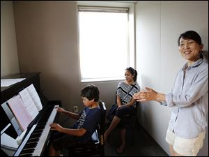 Claire Cho, right,  of the Toledo Symphony applauds as Devyn Penta, 8, practices and his mother Dahwi Pienta watches.