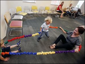 Sarah Bright, right, teaches a Music & Movement class to George Kile, 3, (at center) and David Poeppelmeier, 4, (at left).