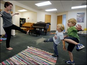 Sarah Bright, left, teaches a Music & Movement class to George Kile, 3, and David Poeppelmeier, 4.
