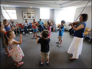 Cheryl Trace, right,  of the Toledo Symphony teaches children how to play the violin.