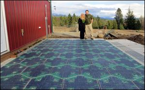 Scott and Julie Brusaw stand for a photo on a prototype solar-panel parking area at their company's business in Sandpoint, Idaho.