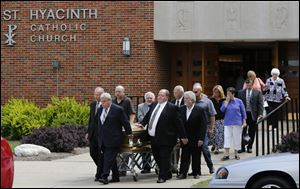 Pallbearers carry Father Gerald Robinson's casket from his funeral service today at St. Hyacinth Church in Toledo.