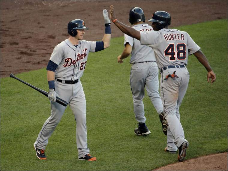 Detroit Tigers' Torii Hunter (48) and Andrew Romine (27) celebrate after Hunter scored on a single by Alex Avila.