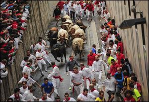 Revelers run ahead of ''FuenteYmbro'' fighting bulls on the way from Santo Domingo street to the bull ring during the running of the bulls Saturday at the San Fermin festival, in Pamplona, Spain.