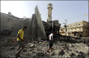 Palestinians gather around the ruins of the Al-Tawfeeq mosque after it was hit by an Israeli missile strike in the Nuseirat refugee camp on Saturday in central Gaza Strip.