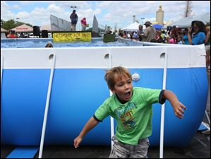 Landon, 4, jumps back to his mother, Diana Koblak of Perrysburg, after watching a dog take a long jump into the pool.