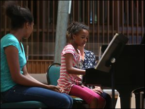 BeInstrumental Foundation students Ronnie Nash, 12, left, and her sister Loretta, 10, gave short performances on their piano during intermission.