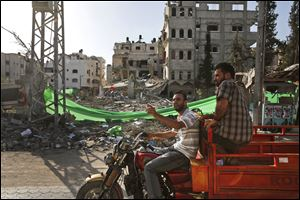 Palestinians drive past a building destroyed by an Israeli strike.