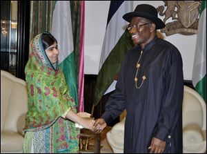 Pakistani activist Malala Yousafzai, left, shakes hands with Nigerian President, Goodluck Jonathan, right, at the Presidential villa, today in Abuja, Nigeria.
