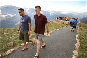 Visitors walk a short trail at a scenic overlook off Trail Ridge Road, above tree-line at Rocky Mountain National Park, west of Estes Park, Colo., Monday, July 14, 2014. Lightning killed two people last weekend just miles apart in the popular park.