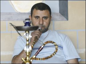 Imad Marouf smokes a lemon and mint hookah in his specialty shop called Hookah Mocha in Monroe, Michigan on April 21, 2010.