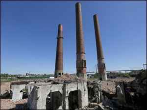 The downtown Toledo skyline is visible behind the remains of the Toledo Edison Acme power plant in the Marina District.
