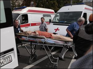 Paramedics carry an injured man out from a subway station after a rush-hour subway train derailment in Moscow.