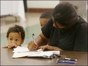 Nathan Barker, 2, and his brother Melvin, Jr., 4, center, keep close to their mother, Lisa, as she fills out forms during the recruitment fair for Toledo Public Schools' preschool program at the former DeVilbiss High School.
