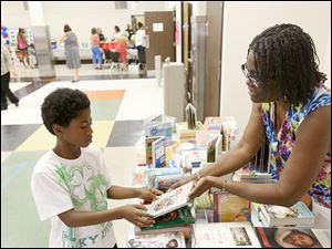 Jadyn McIntosh, 10, left, picks out a book from the book fair, manned by TPS intervention specialist Maudlin Banton, during the first Recruitment Fair at the old DeVilbiss High School in West Toledo.