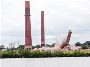 The first smokestack being imploded.
