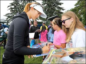 Michelle Wie signs an autograph for Leigh snyder, 14, of Luckey, Ohio.