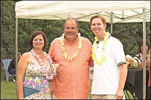 Northwest Ohio Community Shares event chairman Dawn Christen, left, with auctioneer Jack Amlin, and event emcee Shaun Hegarty enjoy the tropical party.