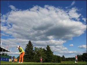 Chella Choi practices her shot on #18 under a bright blue sky.