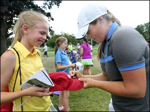 Katie Burnett signs an autograph for Sierra Bengi , 12, of Plainfield, Indiana, during the first round of Marathon Classic.