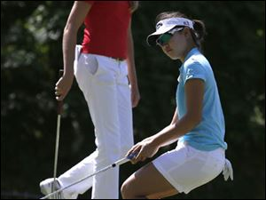 Maude-Aimee Leblanc walks past Kelly Tan as Tan reacts to missing a birdie on Hole 8.