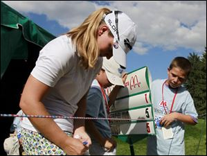 Austin Ernst signs an autograph for her standard bearer Alex Prymas, 10, of Sylvania, after completing her first round.