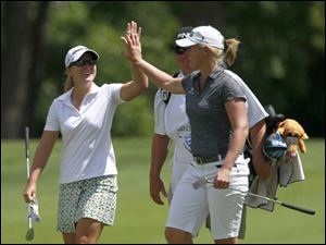Austin Ernst, left, high-fives Jacqui Concolino after Ernst  birdied the18th Hole.