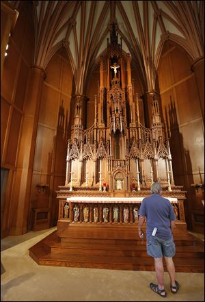 Fred Folger of Toledo stands in front of the altar  during a tour of St. Francis de Sales Chapel downtown.
