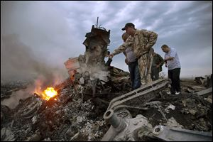 People inspect the crash site of a passenger plane near the village of Hrabove, Ukraine.