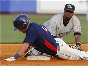 Toledo Mud Hens player Brandon Douglas (11) slides safely into second with a double as Louisville Bats player Ruben Gotay can't make the tag in time.