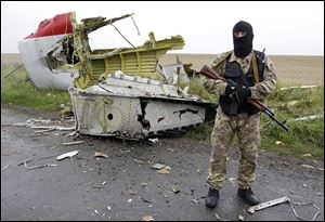 A pro-Russia fighter stands guard at the site of the crashed Malaysia Airlines plane.