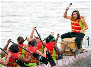 Angelica Diokno right, beats a drum to get her team from Harbor rowing together during a race against TPS.