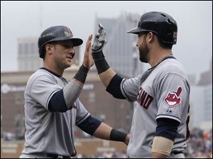 Cleveland Indians' Yan Gomes, left, is congratulated by Jason Kipnis after scoring on a single by teammate David Murphy in the first game.