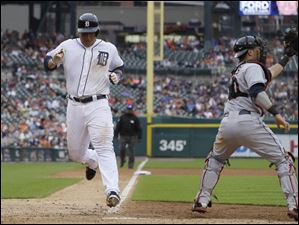Detroit Tigers' Miguel Cabrera scores ahead of the throw to Cleveland Indians catcher Yan Gomes.
