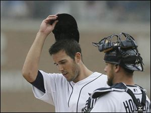 Detroit Tigers starting pitcher Drew VerHagen wipes his face after giving up three runs.