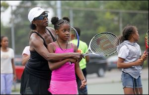 Ethel Parker helps Tatiyana Esmond, 8, with her forehand earlier this month during Ethel Parker's Tennis Camp at Jermain Park in Toledo.