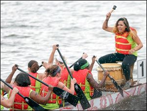 Angelica Diokno, right, beats a drum to get her team from Harbor rowing together.
