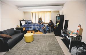 Dana Thomas, left, and Jewel Perry, right, sophomores at University of Toledo, sit in a remodeled single dorm room in MacKinnon Hall.