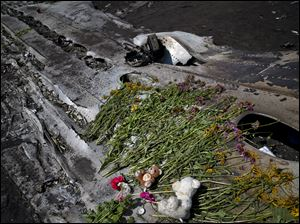 Toys and flowers are placed on the charred fuselage at the crash site of Malaysia Airlines Flight 17 near the village of Hrabove, eastern Ukraine.