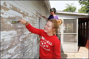 Katie Coburn, 18, of Whitehouse, front, and Tommy Trax, 14, of Berkey work on the home of Gwen Mays. Mrs. Mays has a knee injury and cannot use a ladder so Youth Elect Service members worked at her Toledo home on Friday. The YES group worked on 11 projects in the area.