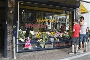 People look at flowers laid in memory of Willem Grootscholten, a victim of flight MH17, who worked for 12 years as a bouncer at the cannabis-selling cafe Andersom in Utrecht, Netherlands.