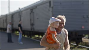 A man holds a baby as he walks next to a refrigerated train loaded with the bodies of victims in Torez, eastern Ukraine, nine miles from  the crash site of Malaysia Airlines Flight 17 on Sunda. Armed rebels forced emergency workers to hand over all 196 bodies recovered from the Malaysia Airlines crash site and had them loaded Sunday onto refrigerated train cars bound for a rebel-held city, Ukrainian officials and monitors said.