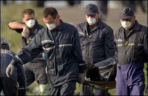 Emergency workers carry the body of a victim at the crash site of Malaysia Airlines Flight 17.