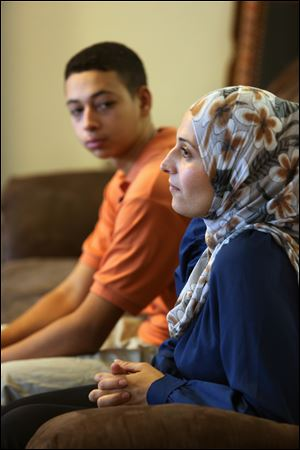 Tariq Abu Khdeir, 15, left, sits with his mother Suha Khdeir during interview in their home Sunday in Tampa.