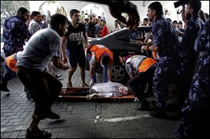 Palestinian medics carry a wounded woman to an emergency room at Shifa hospital Sunday in Gaza City.